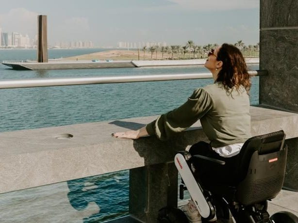 Samata Bullock enjoying view of qatar waterfront seated in electric wheelchair