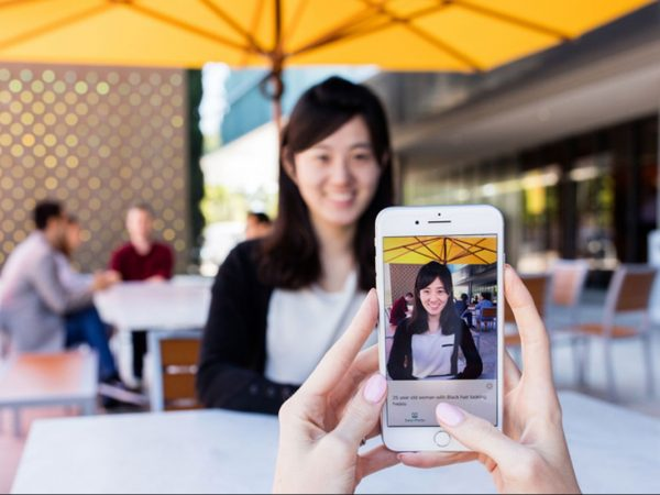 Seeing AI being used to take image of young women in cafe by friend. Text reads 28 year old woman with black hair looking happy
