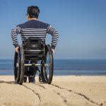 Man in wheelchair using Gecko Traxx system to access beach