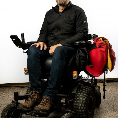 Man seated in electric wheelchair with wheelchair bag system