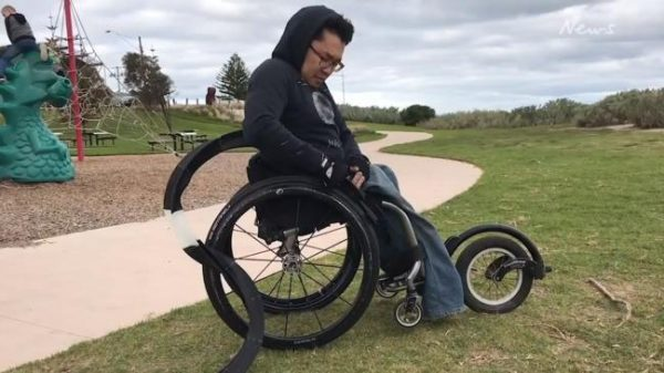 Man seated in wheelchair attaching Gecko Traxx to back wheels of manual wheelchair