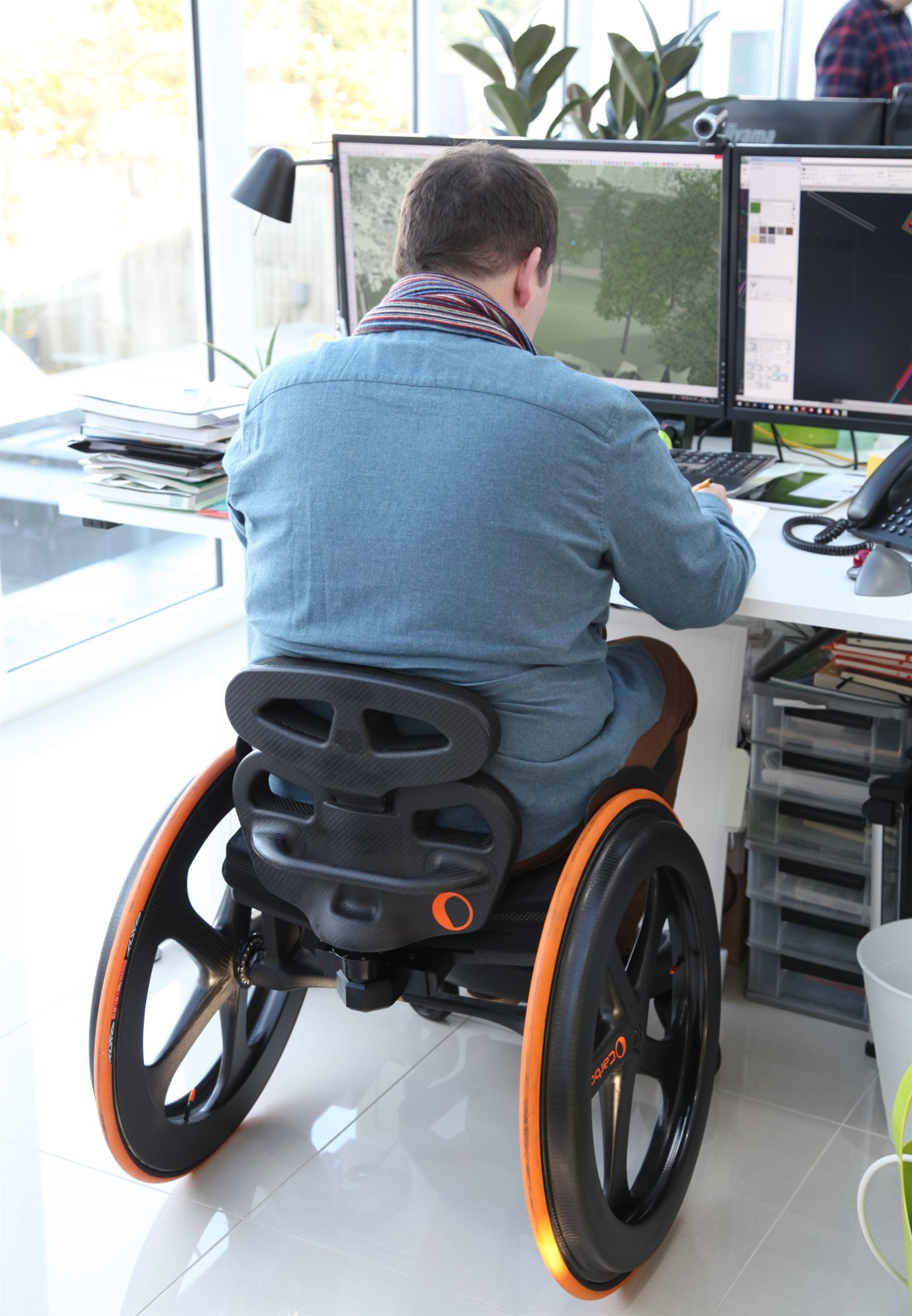 Person seated at desk in Carbon Black Wheelchair