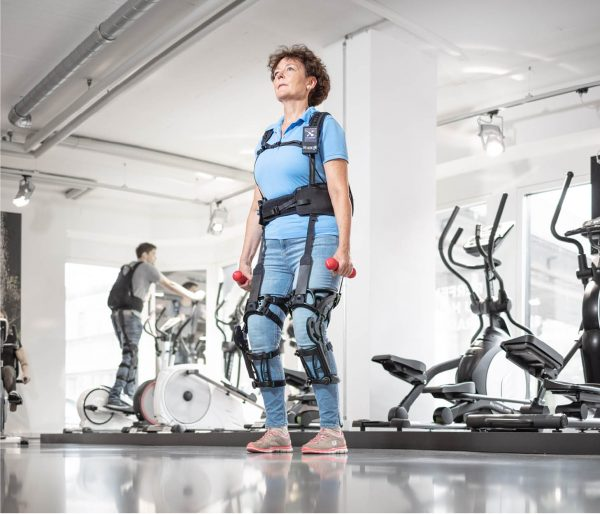 Person Wearing MyoSuit exoskeleton in gymnasium using weights