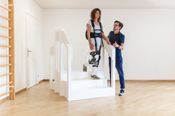 Person with therapist using myosuit to climb stairs