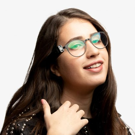 Young person wearing OrCam My Eye on glasses