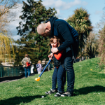 Child playing golf wearing upsee harnesswith adult support