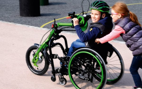 Youth using handbike and towing sister