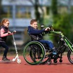 Child using wheelchair hand bike playing with sister on scooter
