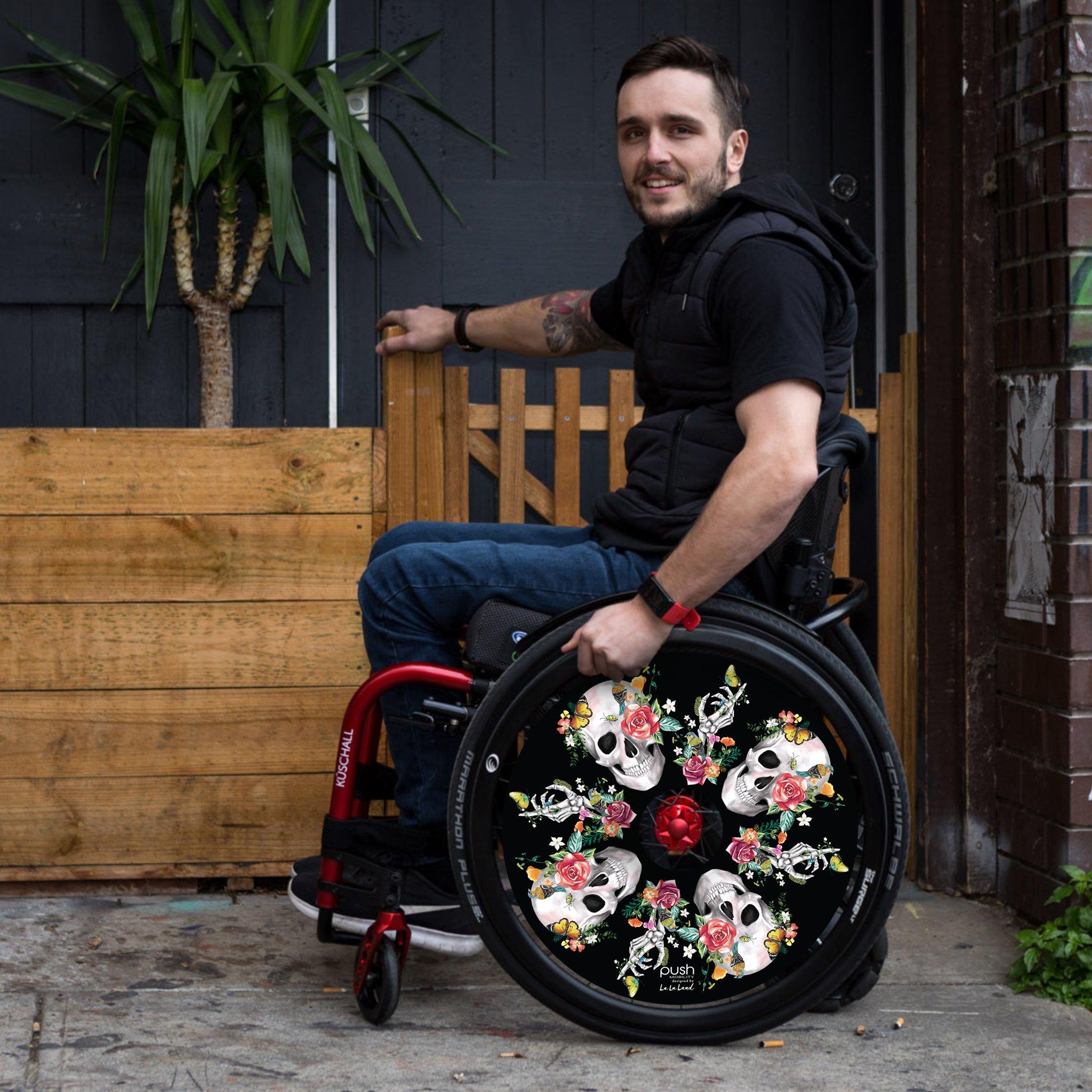 Beautiful Bones Push Hub black wheel cover on wheelchair with man with tatoos