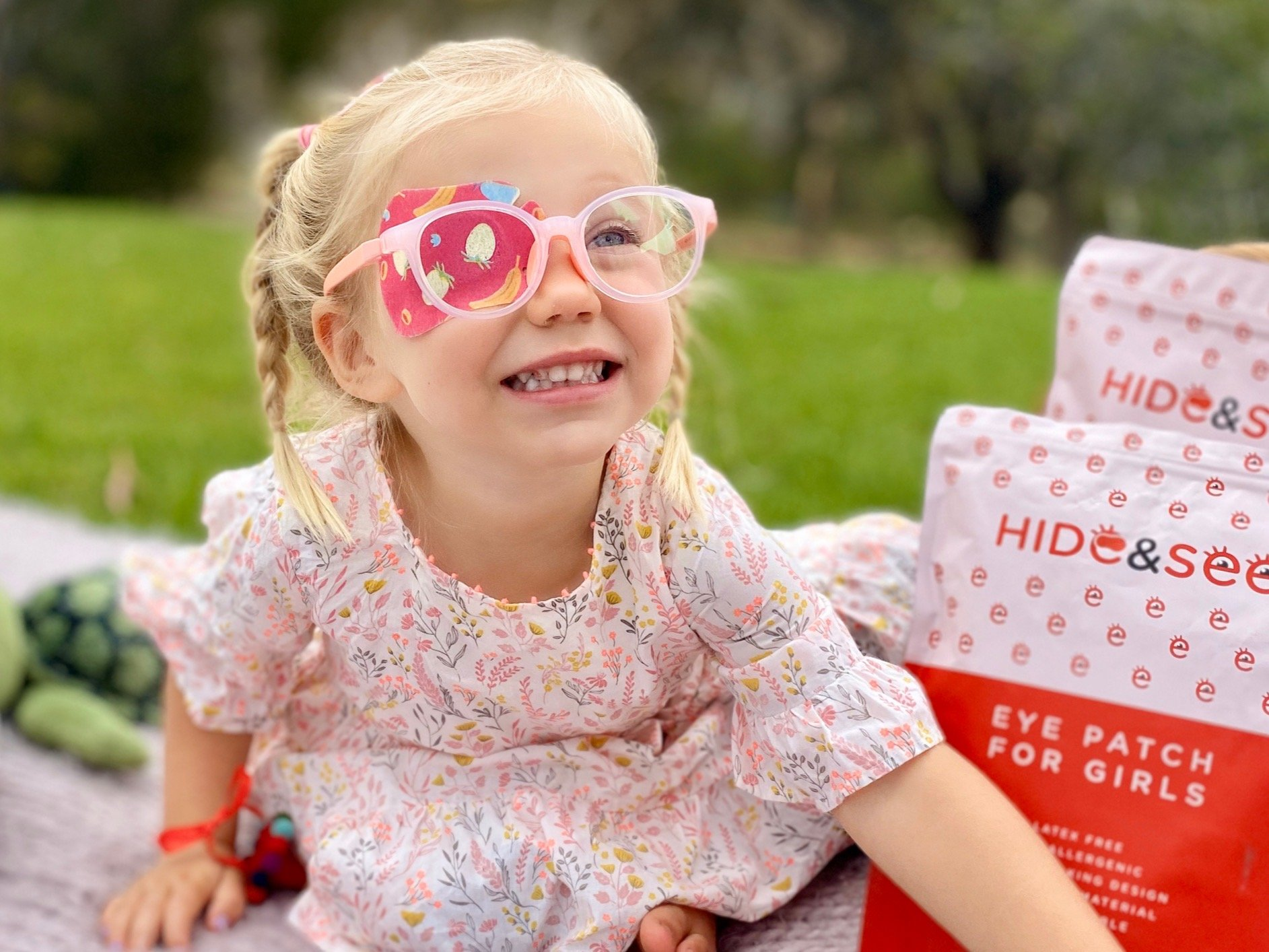 child wearing pink eyepatch and colored glasses
