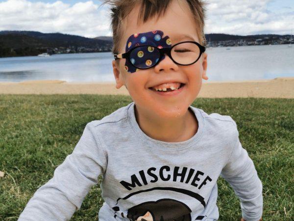Child wearing eye patch under glasses