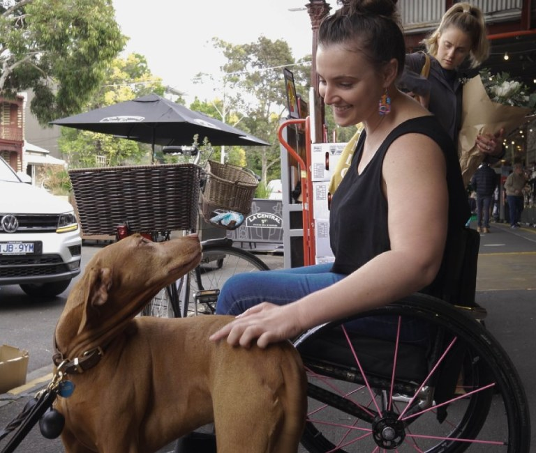 Woman in ROVE wheelchair with dog at cafe