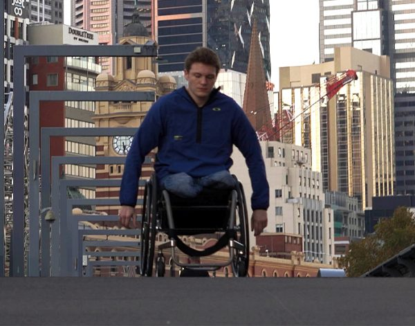 Bilateral amputee propelling ROVE wheelchair through city street