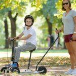 Child using Runner kick bike in park with carer