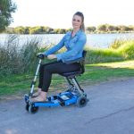 Person riding Blue Luggie Scooter by the lake