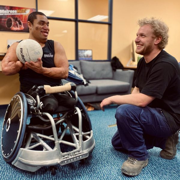 Rugby player using Melrose Rugby Wheelchair talking to technician