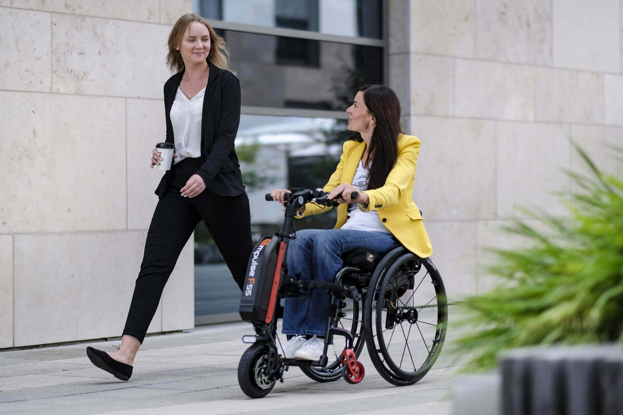 Empulse pull device on manual wheelchair used by woman on way to work with a friend
