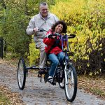 Person riding with family member on Trivel Trike.