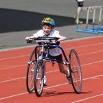 Young person running on athletic track using petra race runner 3 wheel trike