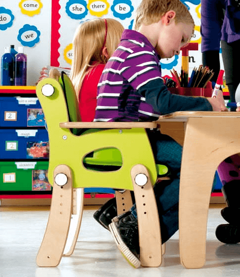 Young child seated in green Leckey pal chair in class