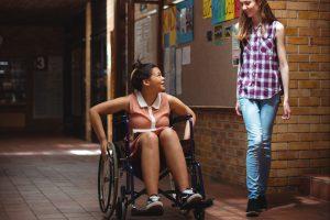 teenagers talking in school hallway, one in wheelchair