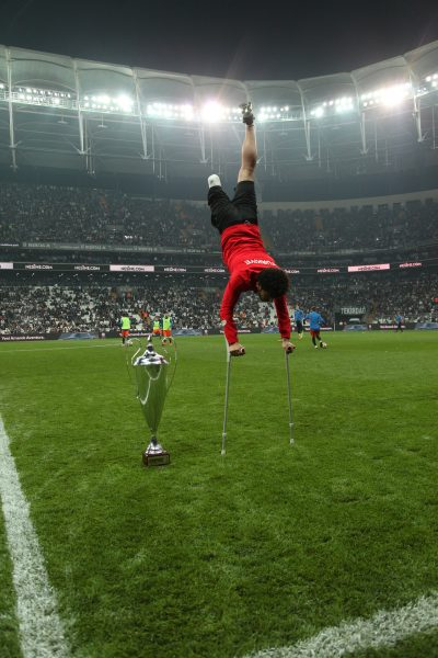 Athlete with above knee amputation doing hand stand on crutches next to championship trophy