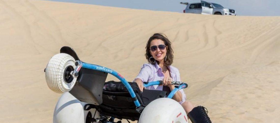 Samanta Bullock sitting in sand dunes beside all terain wheelchair